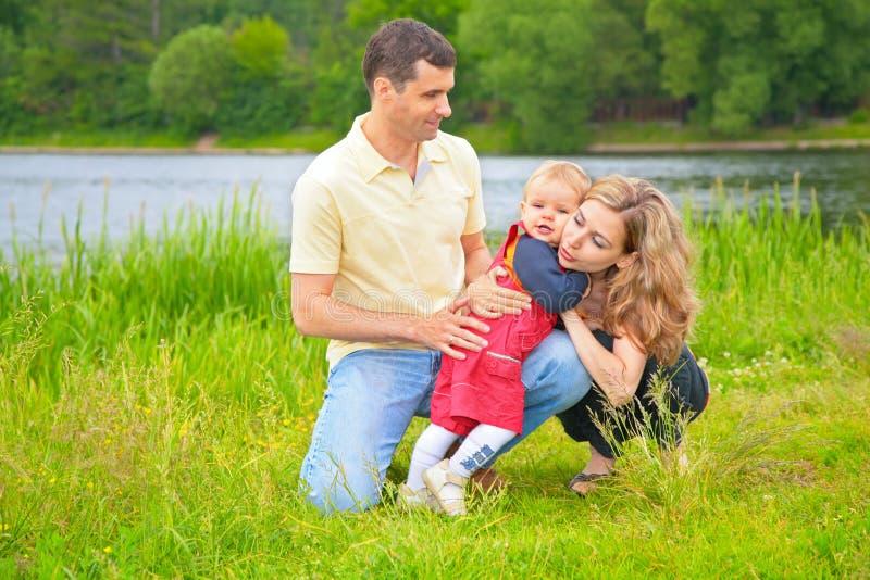 Vader en kind die moeder in openlucht omhelzen royalty-vrije stock foto