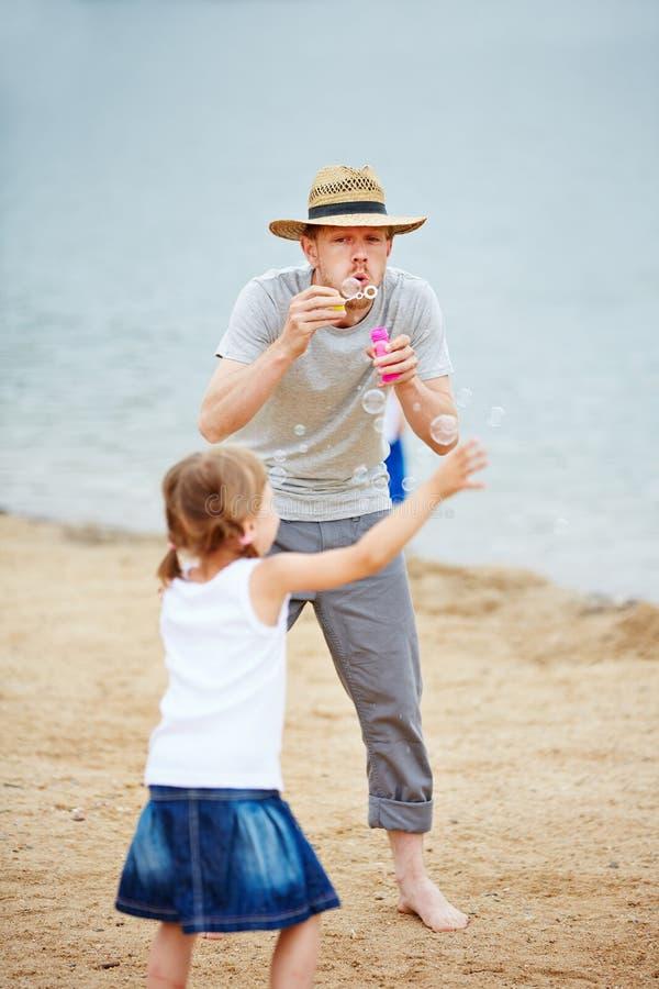 Vader en kind het spelen met zeepbels stock fotografie