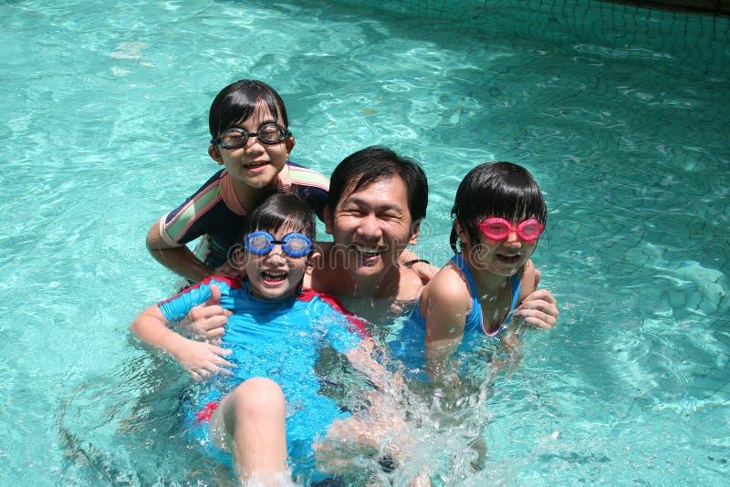 Vader en kinderen in de pool royalty-vrije stock afbeelding
