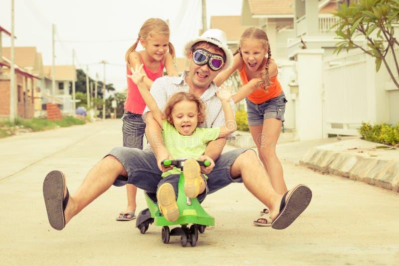 Vader en kinderen die dichtbij een huis spelen royalty-vrije stock fotografie