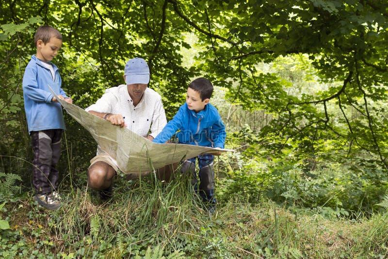 Vader en kinderen die kaart in aard lezen royalty-vrije stock fotografie