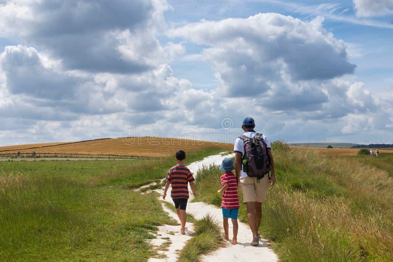 Vader en kinderen die in platteland lopen stock foto's