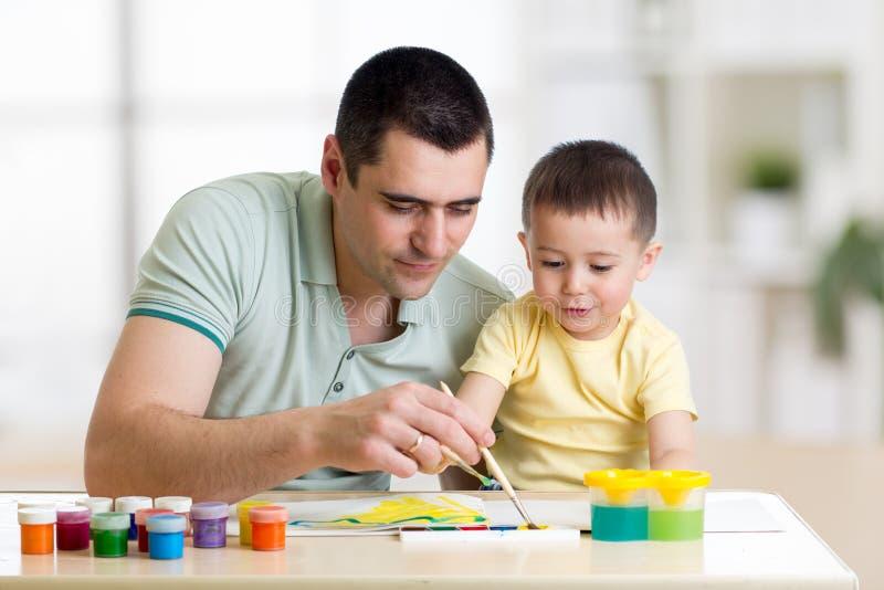 Vader en kindverf samen De papa onderwijst zoon hoe te om correct en mooi op papier te schilderen Familiecreativiteit en royalty-vrije stock foto