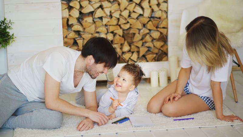 Vader en moeder die hun kind helpen beeld in hun woonkamer trekken royalty-vrije stock afbeeldingen
