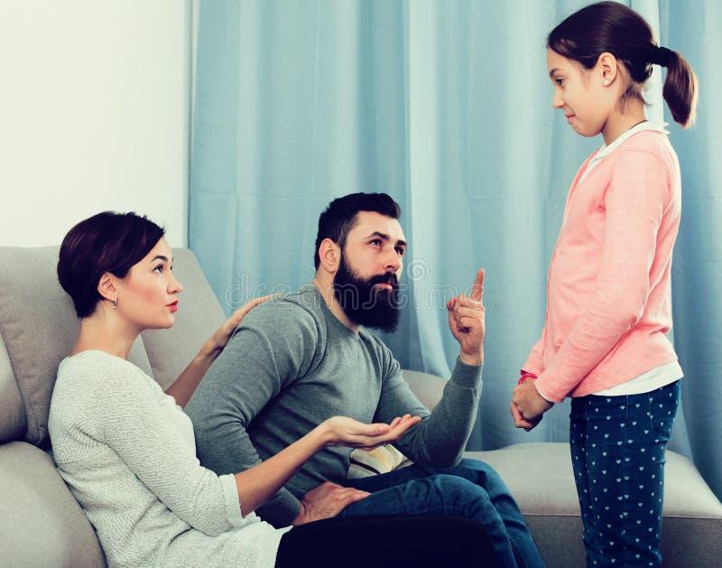Vader en moeder het vertellen van dochter stock afbeelding