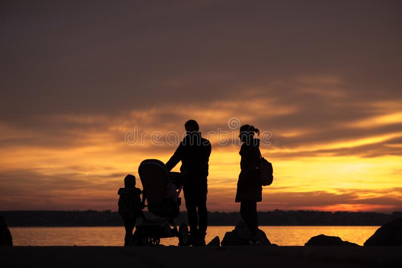 Vader en moeder met een baby in een wandelwagen en kinderen stock foto