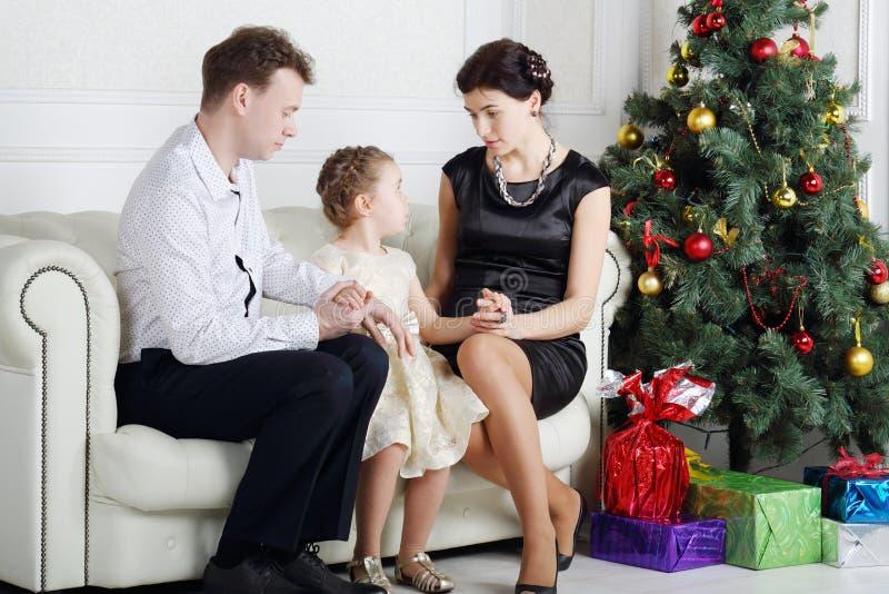 Vader en moederbespreking met dochter op bank dichtbij Kerstboom stock afbeelding