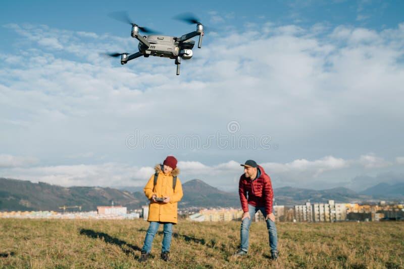 Vader en tiener zoon verkleedde gele jas om een moderne digitale drone te besturen met behulp van een afstandsbediening Moderne t royalty-vrije stock fotografie