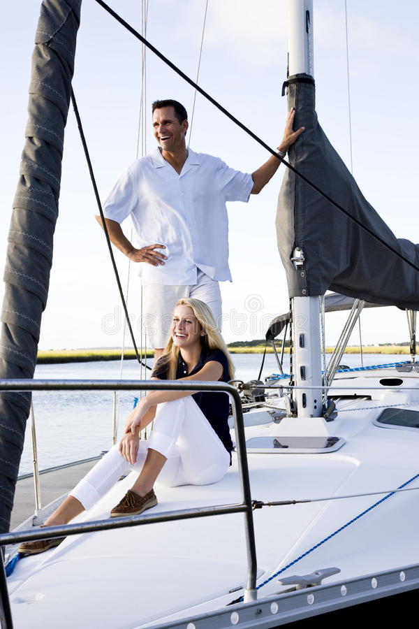 Vader en tienerdochter op zeilboot bij dok stock foto