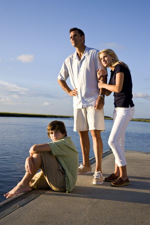 Vader en tienerkinderen op dok door water royalty-vrije stock fotografie