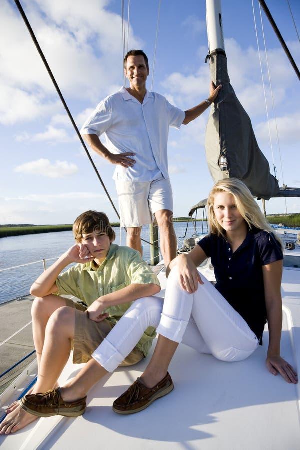 Vader en tienerkinderen op zeilboot bij dok royalty-vrije stock foto