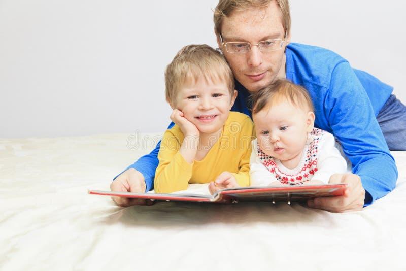 Vader en twee jonge geitjes die boek in bed lezen stock fotografie