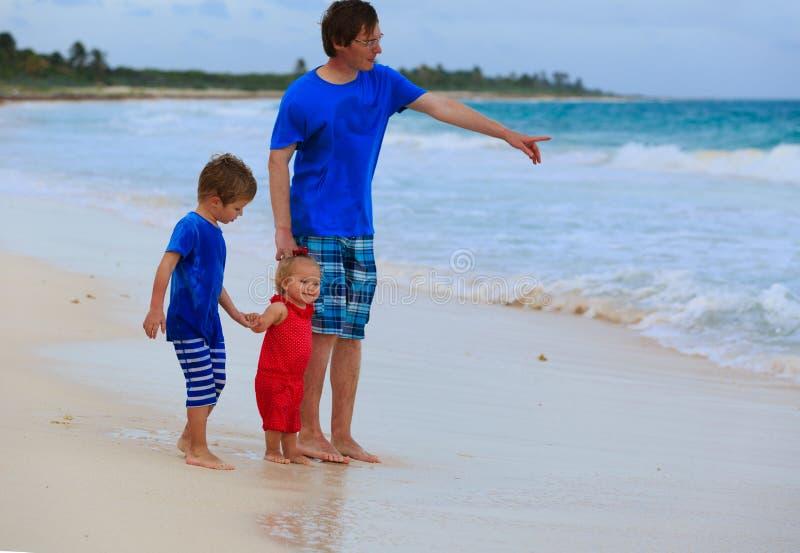 Vader en twee jonge geitjes die op het strand spreken royalty-vrije stock afbeeldingen