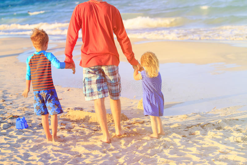 Vader en twee jonge geitjes die op strand lopen royalty-vrije stock foto