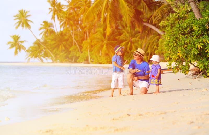 Vader en twee jonge geitjes die shells op strand verzamelen royalty-vrije stock afbeeldingen