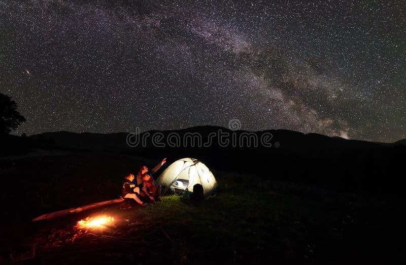 Vader en twee kinderenwandelaars die een rust hebben bij het kamperen in bergen onder het hoogtepunt van de nachthemel van sterre stock afbeeldingen