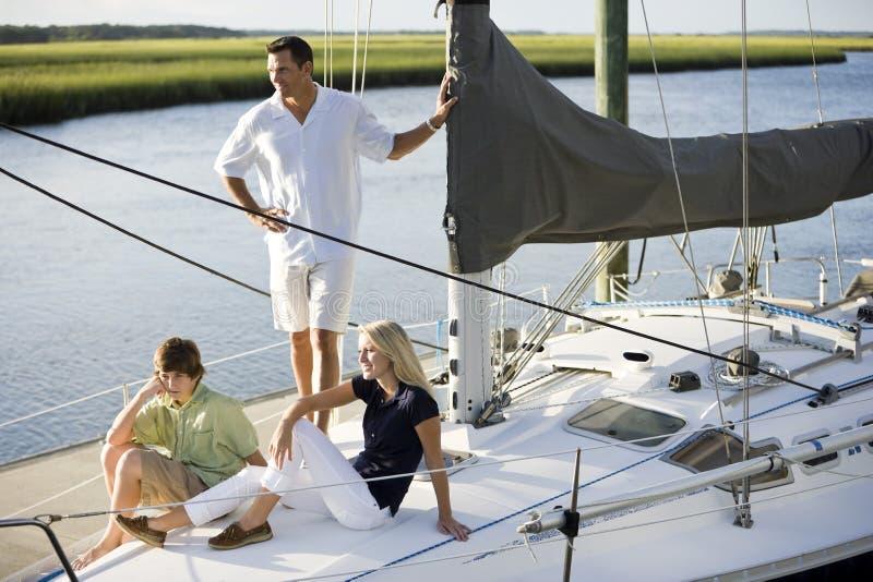 Vader en twee tienerkinderen die op boot ontspannen stock foto's
