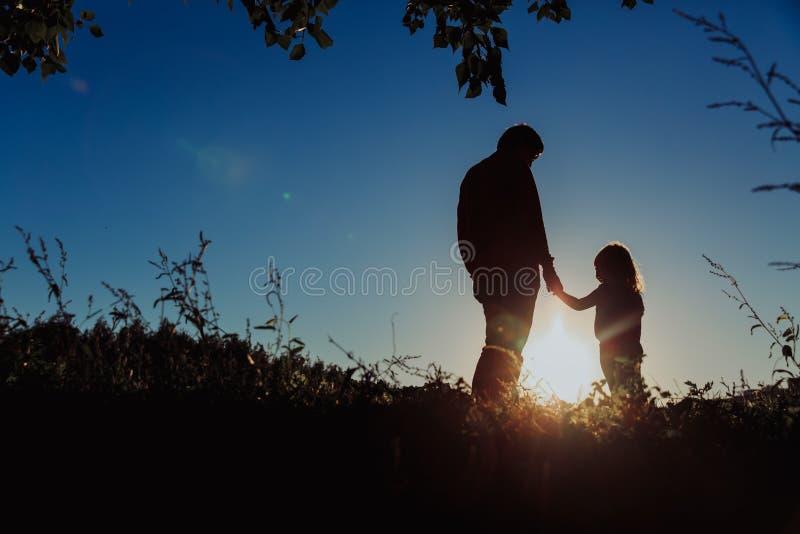 Vader en van weinig dochterholding handen bij zonsondergang royalty-vrije stock foto's