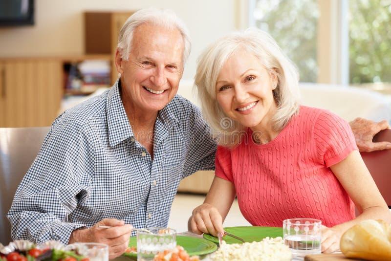 Vader en volwassen dochter die maaltijd delen stock fotografie
