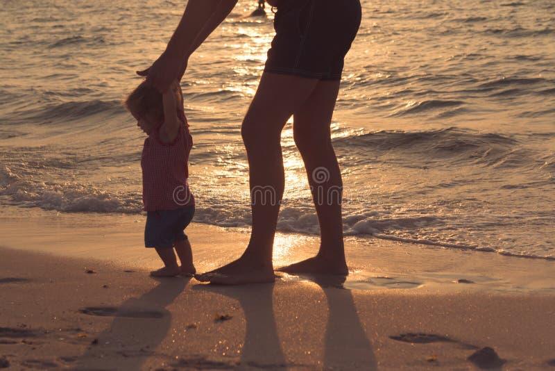 Vader en weinig babydochter die op zandstrand lopen royalty-vrije stock afbeeldingen