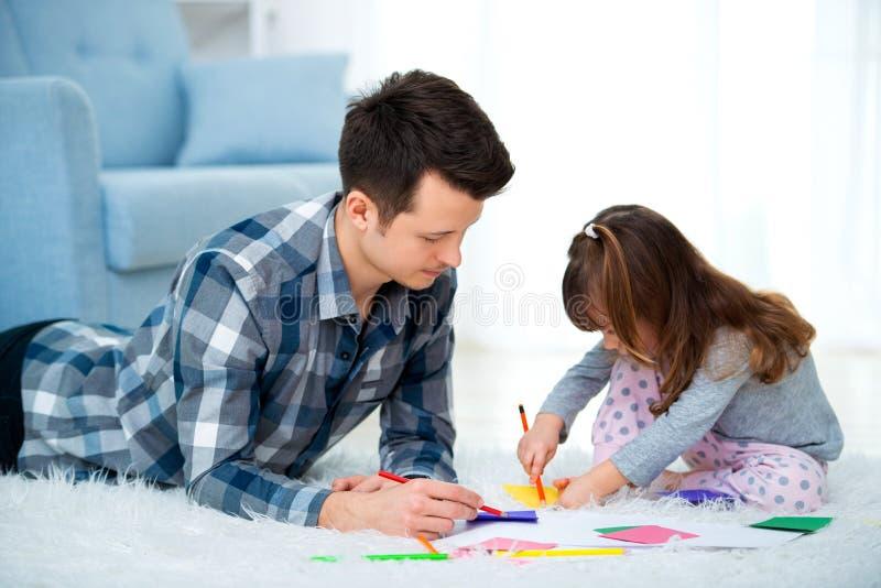 Vader en weinig dochter die de tijd van de kwaliteitsfamilie samen hebben thuis papa met meisje het liggen op warme vloertekening stock afbeeldingen