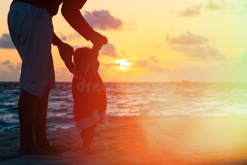 Vader en weinig dochter die op zonsondergangstrand lopen stock afbeelding