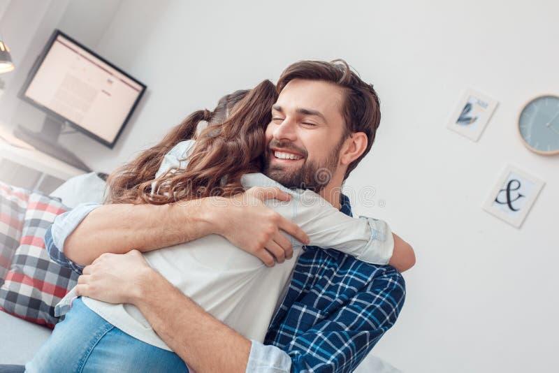 Vader en weinig dochter die thuis de mens zitten die gelukkig meisje koesteren stock foto's