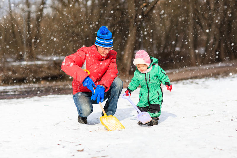 Vader en weinig dochter gravende sneeuw in de winter stock afbeeldingen
