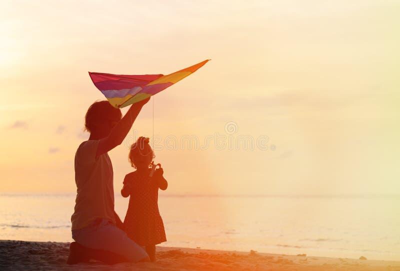 Vader en weinig dochter vliegende vlieger bij zonsondergang royalty-vrije stock fotografie
