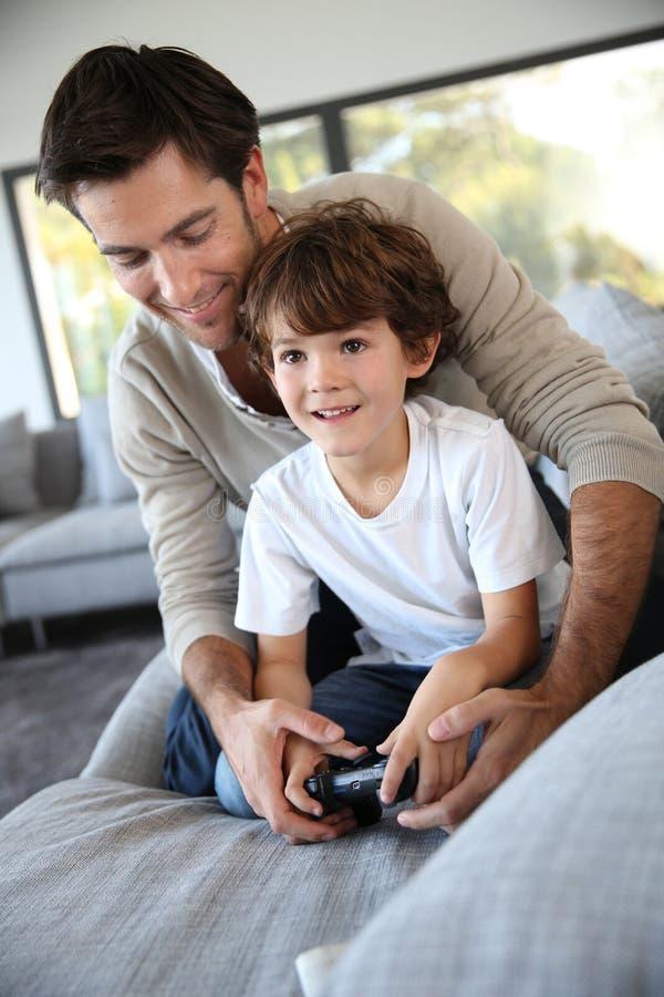 Vader en weinig jongen het spelen videospelletje stock afbeeldingen