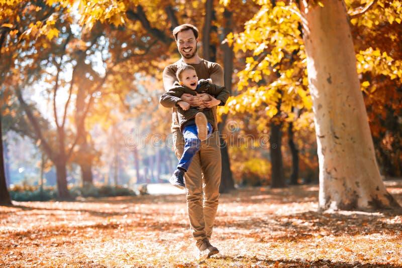 Vader en weinig zoon die en pret in openlucht over de achtergrond van het de herfstpark spelen hebben stock foto