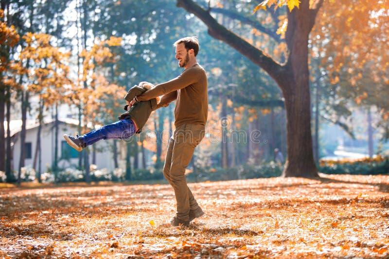 Vader en weinig zoon die en pret in openlucht over de achtergrond van het de herfstpark spelen hebben royalty-vrije stock foto's