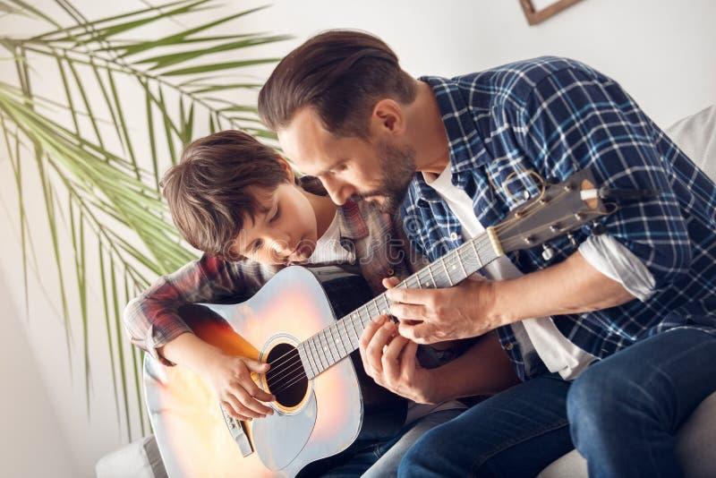 Vader en weinig zoon die thuis op bankjongen zitten met gitaarpapa die nadenkende snaren tonen stock afbeeldingen