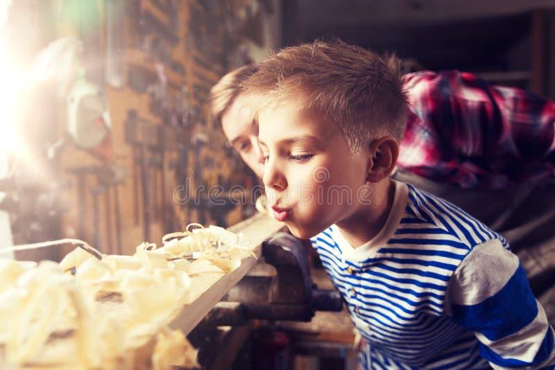 Vader en weinig zoon met houten plank op workshop royalty-vrije stock afbeeldingen