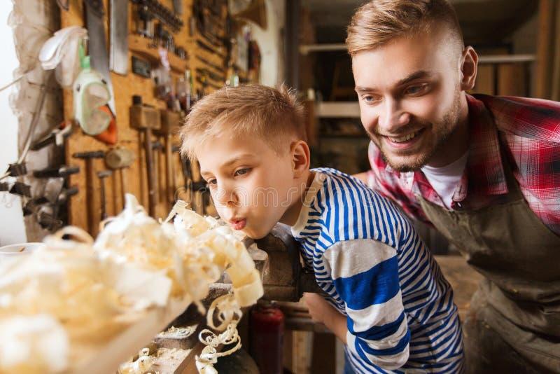 Vader en weinig zoon met houten plank op workshop stock fotografie