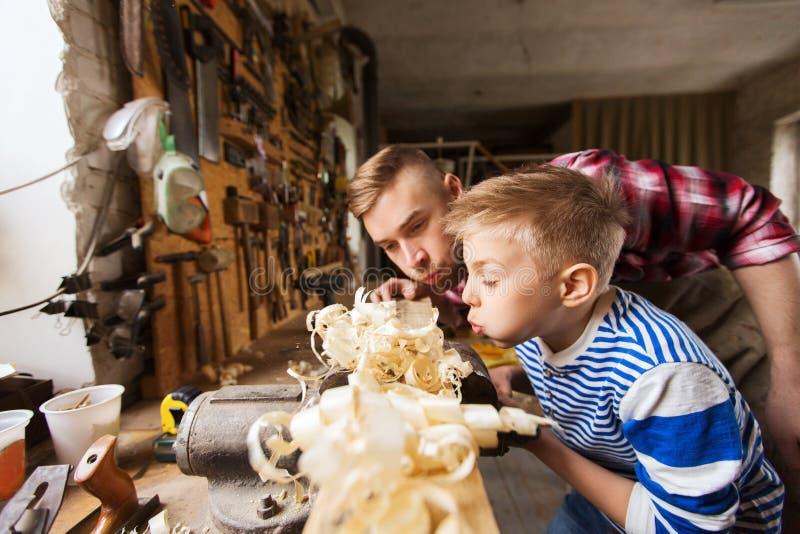 Vader en weinig zoon met houten plank op workshop stock foto