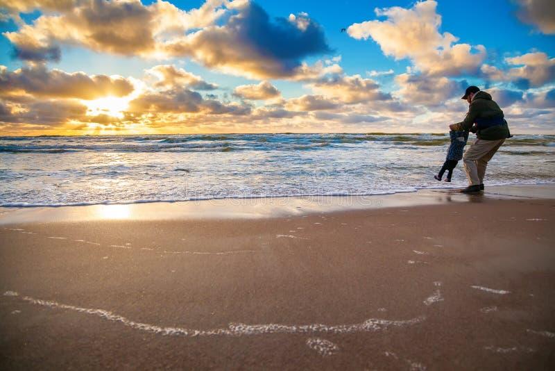 Vader en zijn kleine dochter die met golven spelen royalty-vrije stock foto