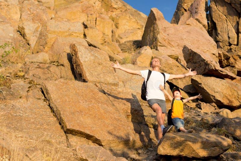 Vader en zijn kleine zoon op een rotsachtige berg stock afbeeldingen