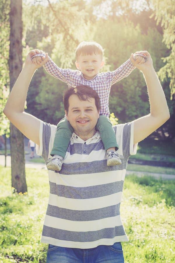 Vader en zijn twee jaar oude zoons op zijn schouders royalty-vrije stock afbeelding