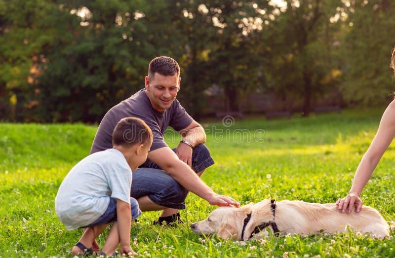 Vader en zijn zoon die met hond in park spelen - de gelukkige familie is hav royalty-vrije stock afbeelding