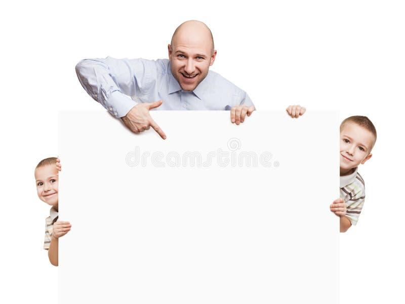 Vader en zonen die leeg teken of aanplakbiljet houden royalty-vrije stock afbeelding