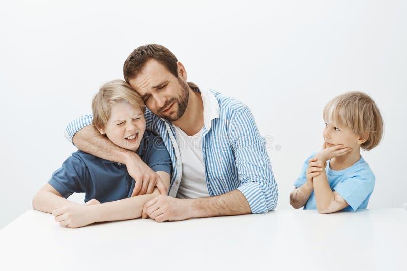 Vader en zonen die onplezierig geheim van jongere jongen verbergen Portret van somber ongelukkig en papa en kind die koesteren sc royalty-vrije stock foto's