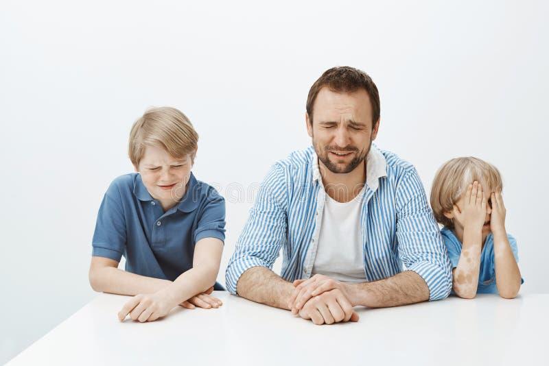 Vader en zonen voelen verstoord terwijl mamma op het werk Portret van hongerige ontstemde Europese familie van mannelijke jongens royalty-vrije stock afbeeldingen