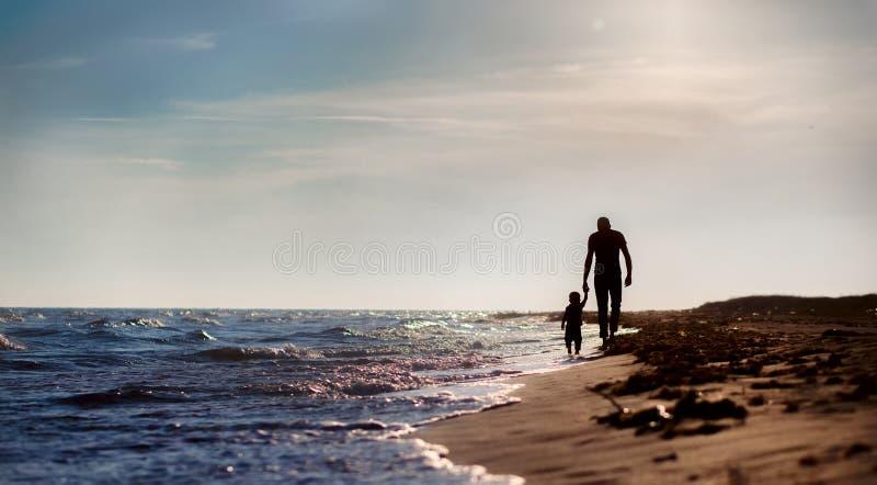 Vader en zoon aan het overzees bij zonsondergang royalty-vrije stock fotografie
