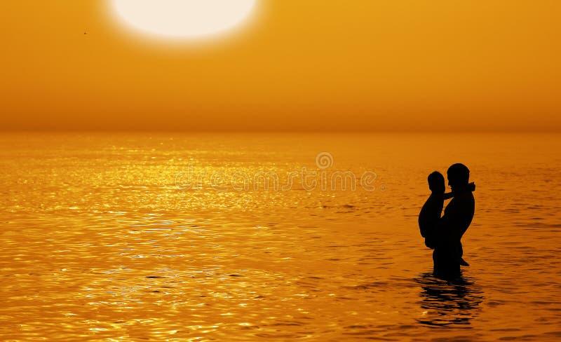 Vader en zoon aan het overzees bij zonsondergang stock afbeelding