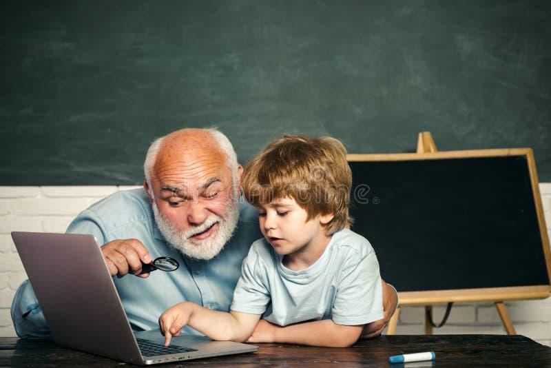 Vader en zoon Basisschooljong geitje en leraar met laptop in klaslokaal op school tutoring Dank u leraar stock afbeeldingen