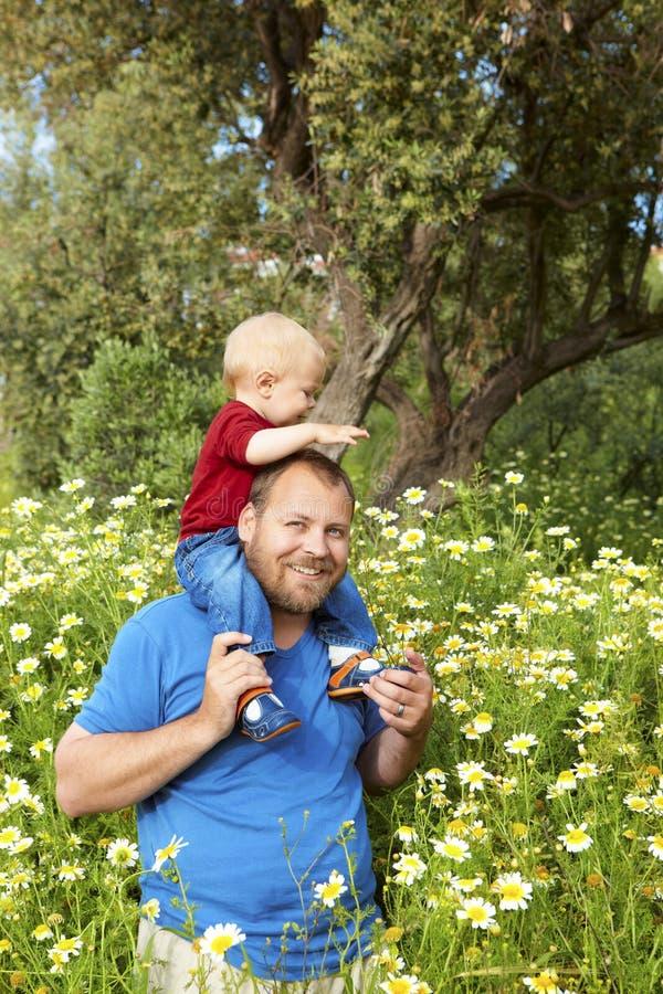 Vader en zoon in bloemen royalty-vrije stock afbeeldingen
