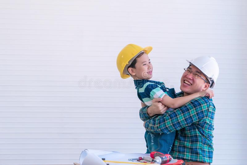 Vader en zoon bouwpak knuffelen terwijl ze in de verbetering van hun woning werken voor het concept van gezinsverbondenheid en li stock fotografie