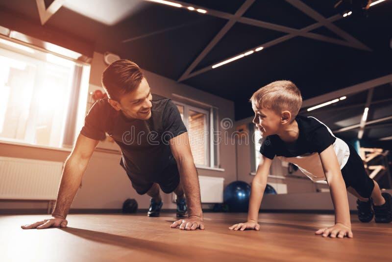 Vader en zoon in de gymnastiek De vader en de zoon brengen samen tijd door en leiden een gezonde levensstijl stock afbeeldingen
