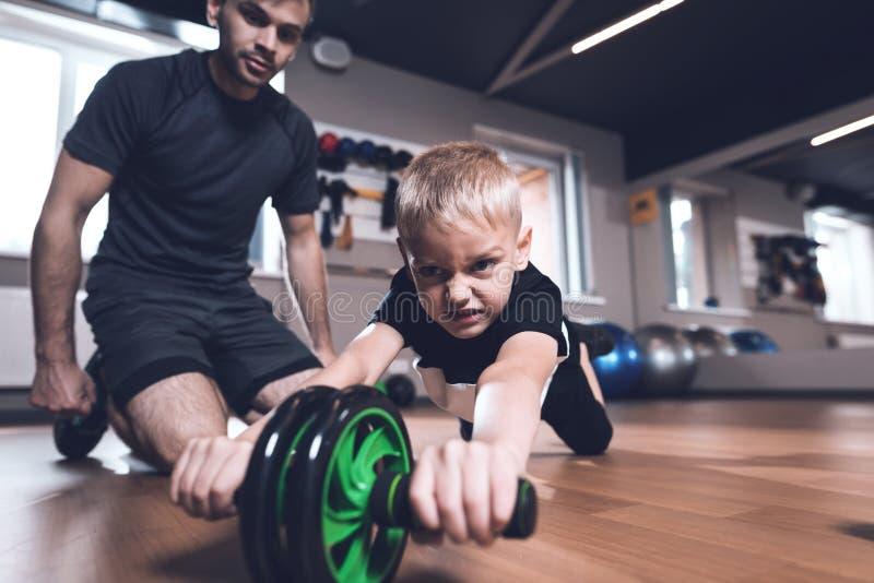 Vader en zoon in de gymnastiek De vader en de zoon brengen samen tijd door en leiden een gezonde levensstijl royalty-vrije stock fotografie